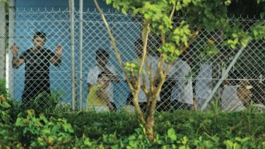 Asylum seekers behind wire on Manus Island last year.