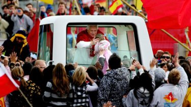 A blessing for some ... Pope Benedict meets a young follower at World Youth Day, which cost $86 million.