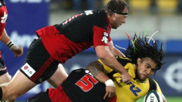 Ma a Nonu of the Hurricanes is tackled by Sean Maitland.