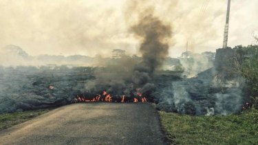 On the move: The lava flow from the Kilauea volcano crosses Cemetery Road near the village of Pahoa.