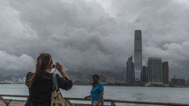 Chinese tourists take pictures in front of the Kowloon skyline during a thunderstorm in Hong Kong caused by Typhoon Kalmaegi on Tuesday.