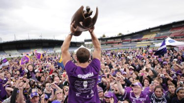 Melbourne Storm second-rower Ryan Hoffman holds aloft the 2009 NRL premiership trophy in front of the team's loyal fans in Melbourne.