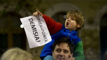 """A child holds a piece of paper that reads """"Oprea-Ponta-Resignation"""" during a protest demanding the resignations of Interior Minister Gabriel Oprea and Prime Minister Victor Ponta in Bucharest, Romania, on Monday."""