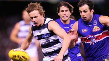 The chase: Geelong's Mitch Duncan and Bulldog Brian Lake battle for possession last night.
