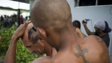 Cuban migrants set up a makeshift barber shop outside the immigration office in Penas Blancas.