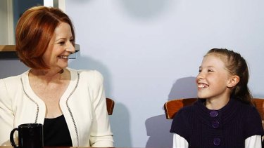 Prime Minister Julia Gillard discusses the carbon tax with Hannah Cochrane at the family's home in west Sydney yesterday.