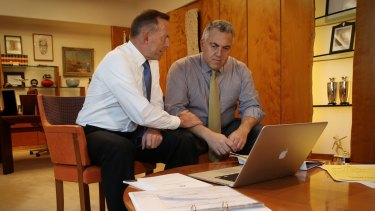 Prime Minister Tony Abbott poses with the Treasurer Joe Hockey as they look through the Budget papers in May 2015.
