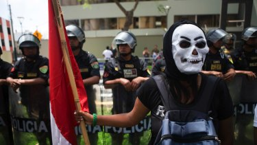 A protester, wearing a skeleton mask, holds a Peruvian national flag during a rally against the Trans-Pacific Partnership in Lima, Peru.