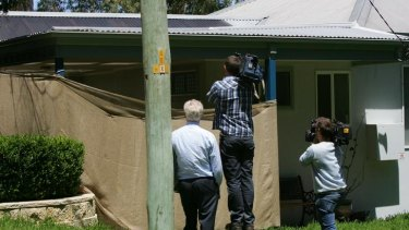 Members of the press try to see inside the boy's house at Morisset Park.