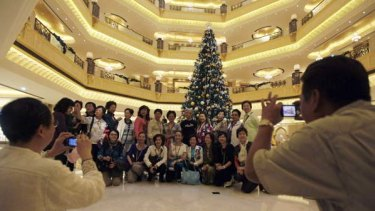 Tourists pose to have their photos taken in front of a Christmas tree which has been decked out with $11 million worth of gold.