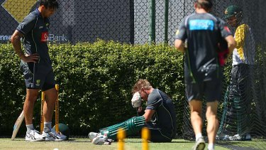 David Warner is disconsolate after being struck on the left hand by Mitchell Johnson during training session at the WACA.
