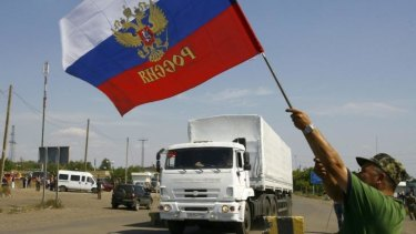 A resident holds a Russian flag as a truck from the previous aid convoy crosses the Ukrainian border. Moscow has vowed to send another.