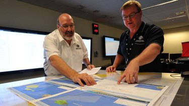 Mike Barton, rescue co-ordination chief of the Australian Maritime Safety Authority, left, looks over maps of the Indian Ocean with Alan Lloyd, manager of search and rescue operations. at the Rescue Co-ordination Centre in Canberra