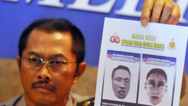 Indonesian police spokesman Nanan Sukarna shows images of the suicide bombers.