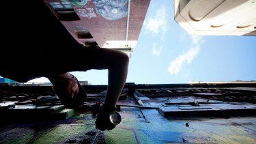 Looking up in Hosier Lane? Graffiti artist The Kromster paints on the wall of the building to be demolished.