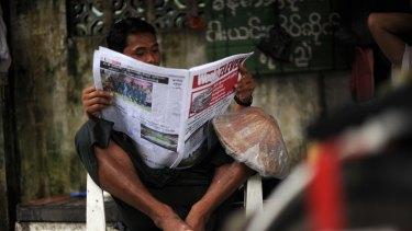 A Myanmar man reads a local newspaper in Yangon.