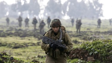 An Israeli soldier from the Golani brigade takes part in training near the city of Katzrin in the Israeli-occupied Golan Heights. An Israeli helicopter strike in Syria killed a commander from Iran's Revolutionary Guard and the son of the group's late military leader Imad Mughniyeh, Hezbollah said.
