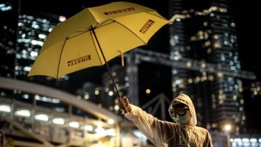 A pro-democracy activists stands with a yellow umbrella