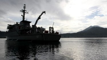 The HMAS Yarra off Rabaul on Wednesday. Wreaths and flowers were thrown overboard in a dawn service marking 100 years since the AE1 disappeared without trace.