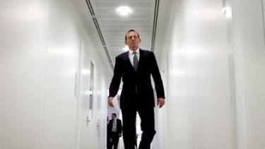 Tony Abbott strides the corridors of parliament.