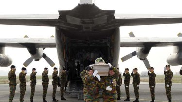 Sad and solemn ... soldiers carry a child's white coffin.