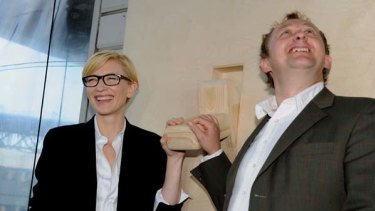 """Sydney Theatre Company  artistic directors Cate Blanchett  and Andrew Upton  use a wooden switch to make a symbolic """"switch on"""" of a massive solar array on the roof of STC's home base in Sydney."""