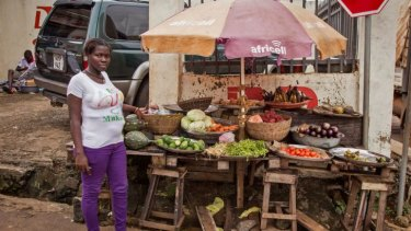 A trader looks out from her make shift shop, selling various ingredients for many local dishes, with chili peppers which have doubled in price during the time of the Ebola virus crisis in the city of Freetown, Sierra Leone. There is a ban on sale of bushmeat.