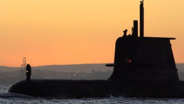 The submarine HMAS Collins surfaces at sunrise.