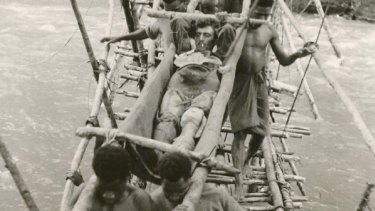 A wounded Australian soldier being carried by local men in Papua New Guinea during World War II.