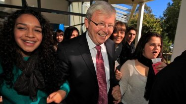Linked in ... Kevin Rudd being escorted to his car by members of the National Indigenous Youth Parliament at Eagle Hawk Resort near Canberra.