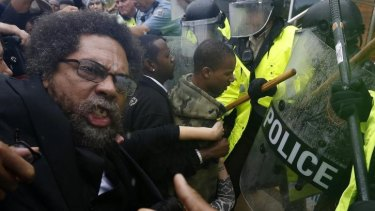 Rough treatment: Activist Cornel West is knocked over during a scuffle with police during a protest at the Ferguson Police Department.