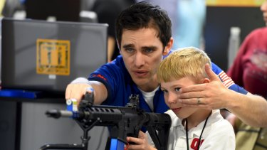 Brett Throckmorten of Barnes Bullets shows Logan Wingo how to sight down an electronic rifle in the trade booth area during the National Rifle Association's annual meeting in Nashville, Tennessee.