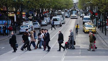 Pedestrians and cars mix it on Swanston Street.