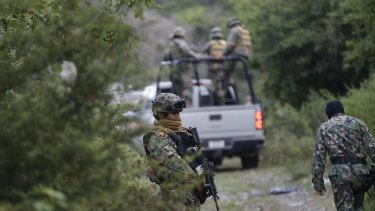 Soldiers of the Mexican Navy stand guard near a newly discovered mass grave outside the mountain town of Cocula.