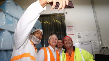 Prime Minister Malcolm Turnbull poses for a selfie with workers at  Grove Fruit Juice in Brisbane.