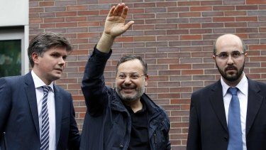 Al Jazeera's journalist Ahmed Mansour (centre) reacts after being released in Berlin, Germany.