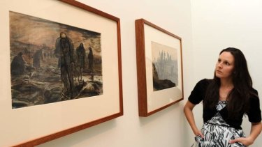 Assistant curator at the Australian War Memorial, Dr. Emma Kindred, with two paintings by WWII official war artist, Alan Moore at an exhibition on show in the WWII galleries. The two images portray activities at the Bergen-Belsen concentration camp, Germany on the day of its liberation.