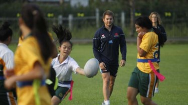 Having a ball … Australia and Waratahs winger Drew Mitchell watches as the Prairiewood High School girls show off their skills yesterday morning in Wetherill Park.