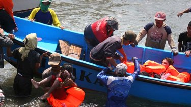 Rescuers assist survivors arriving on fishing boat at the wharf of Cidaun, West Java on July 24, 2013 after an Australia-bound boat carrying asylum-seekers sank off the Indonesian coast.