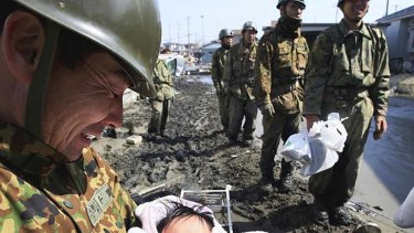 A little ball of hope ... a four-month-old baby girl is carried to safety in Ishimaki by the Japanese Self Defence Force.
