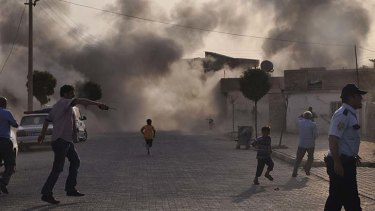 Cross-border attack ... residents of Akcakale, southern Turkey, scramble for safety after a mortar strike fills its streets with smoke.