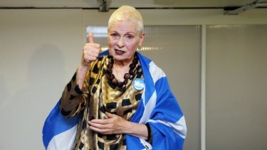 Wearing a yes badge and a Scottish flag, designer Vivienne Westwood gestures backstage before the presentation of her Vivienne Westwood Red Label spring/summer 2015 collection during London Fashion Week.