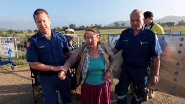 Clash: Paramedics assist a woman at the protest site.