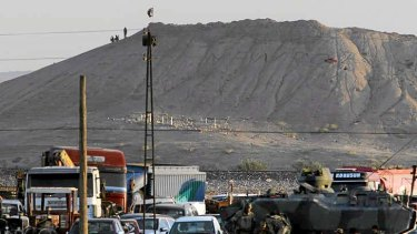 Turkish forces patrol the border as militants with the Islamic State group are seen after placing their group's flag on a hilltop at the eastern side of the town of Kobane.