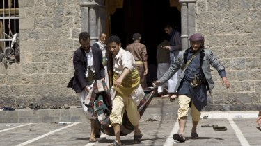Yemenis carry the body of a man killed in the bombing out of the mosque in Sanaa.