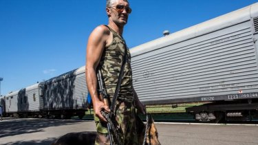 A pro-Russian rebel guards the train holding the bodies of MH17 victims.