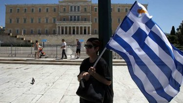 Protesting against austerity ... a woman holds Greek and small Cypriot flags during a rally in front of the Parliament in Athens.