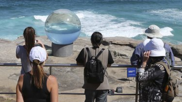 Visitors gaze at <i>Horizon</i> by Lucy Humphrey at the <i>Sculpture By The Sea</i> exhibition at Bondi.
