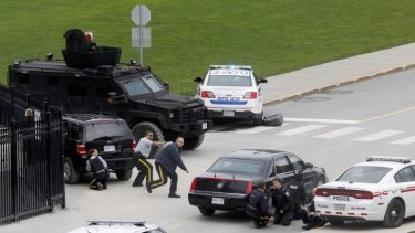 Police officers take cover near Parliament Hilll following the shooting.