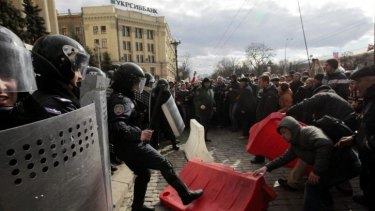 A Ukrainian riot police officer tries to prevent a pro-Russian demonstrator from picking up part of a road block during a rally near the regional administrative building in Kharkiv, Ukraine.
